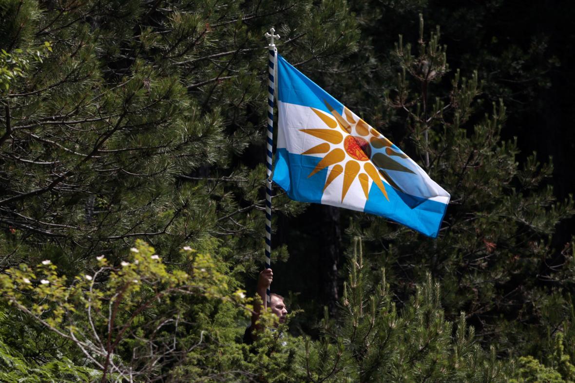 Protestant drží řeckou vlajku se symbolem Verdžinského slunce