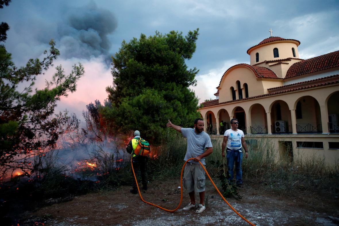 Lidé se snaží zastavit požár u kostela ve městě Rafina