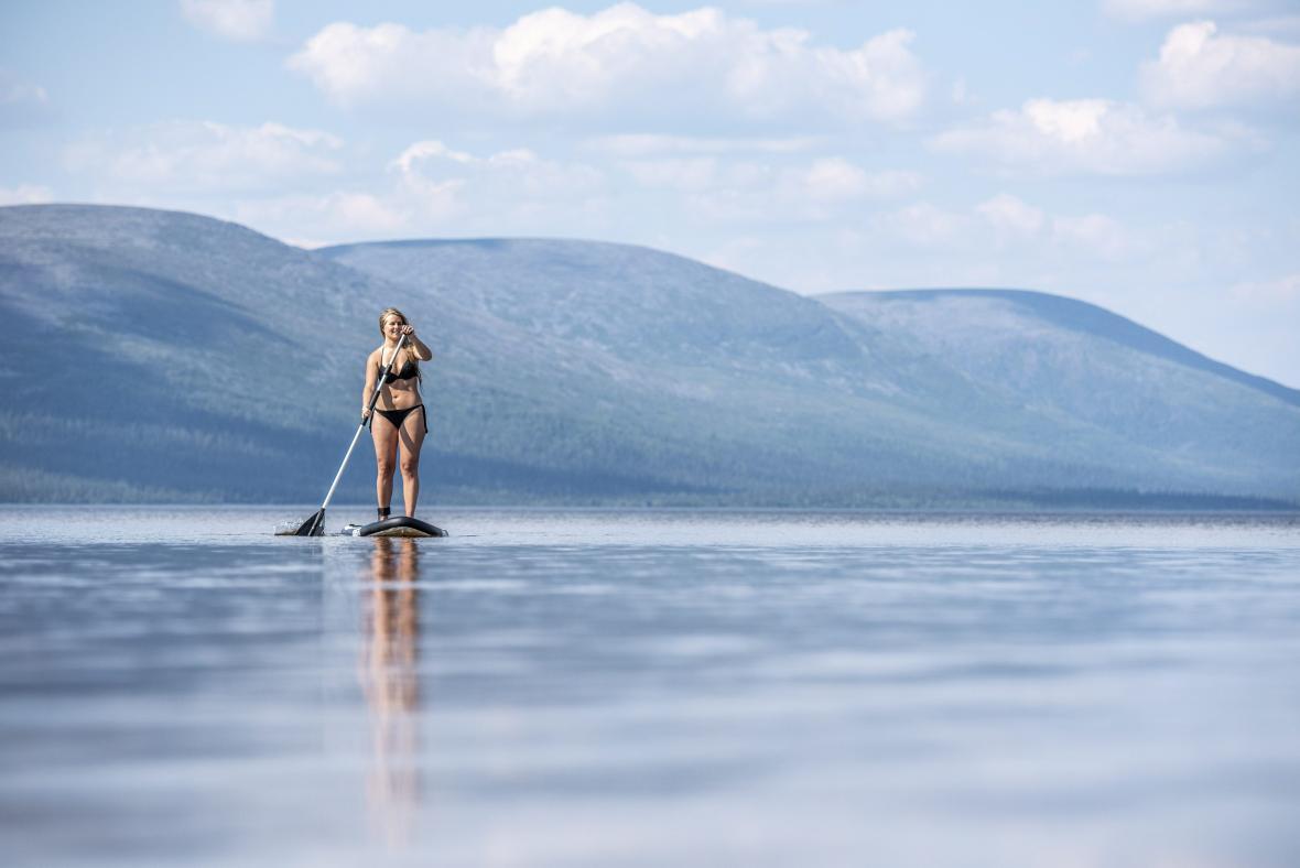 Žena na paddleboardu na jezeře Pallasjarvi. To se nachází v laponské části Finska nad severním polárním kruhem