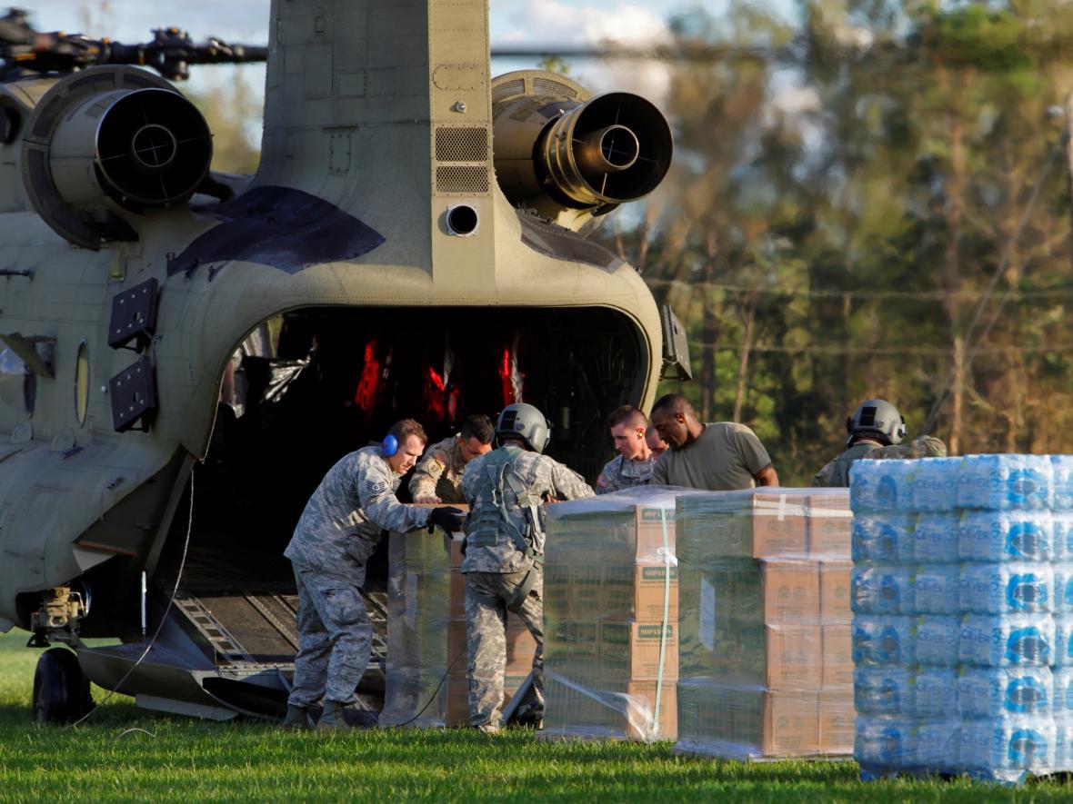 Vojáci vykládají vodu a potraviny pro lidi v obci izolované povodní z vrtulníku CH-47 Chinook