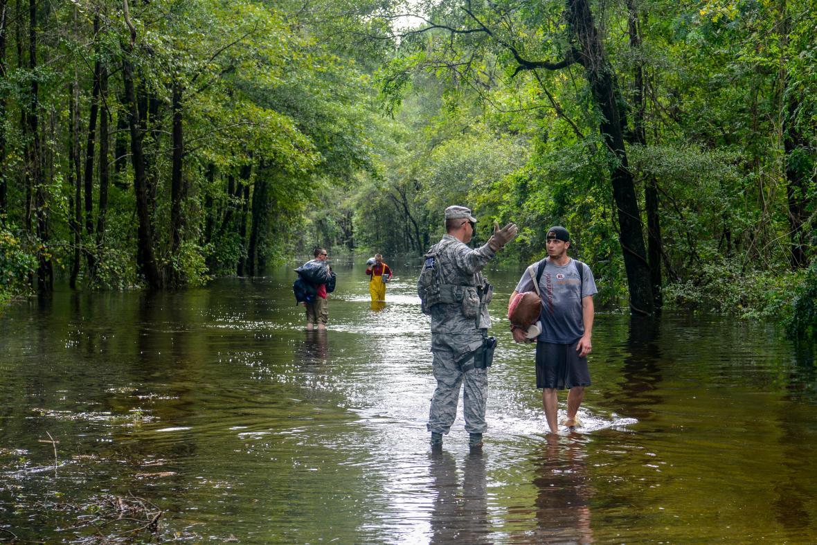 Voják amerického letectva pomáhá evakuovaným lidem