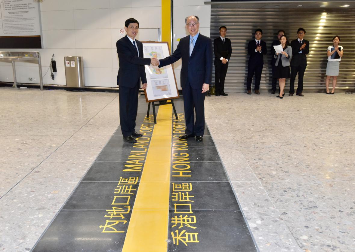 Zástupci Hongkongu a pevninské Číny u linie oddělující čínskou a hongkongskou část nádraží