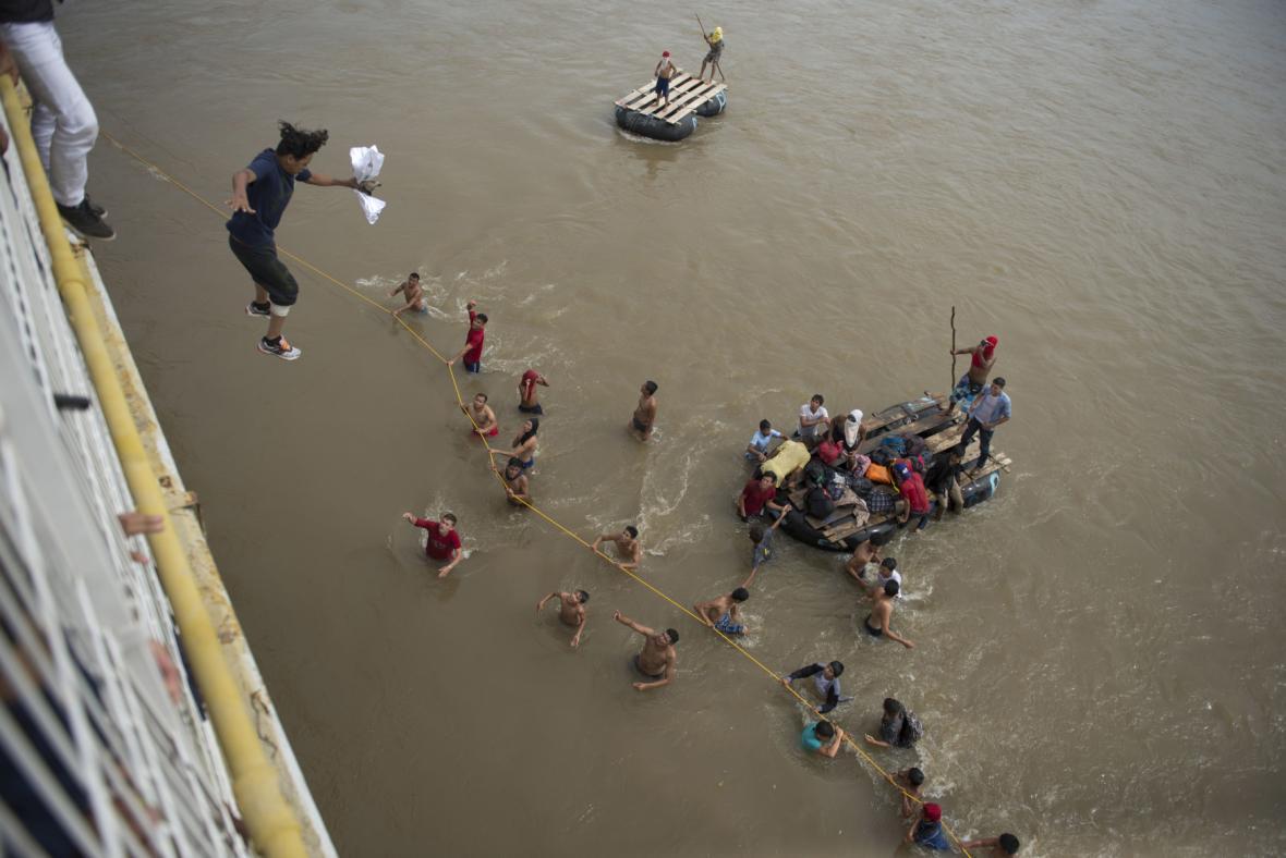 Někteří migranti skáčou do řeky Mezi Mexikem a Guatemalou a snaží se přes ni dostat pomocí lana