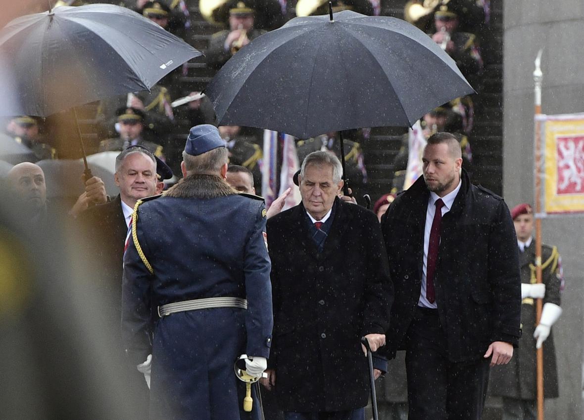 Prezident Miloš Zeman (druhý zprava) a slovenský prezident Andrej Kiska poslouchají hlášení na pietním aktu