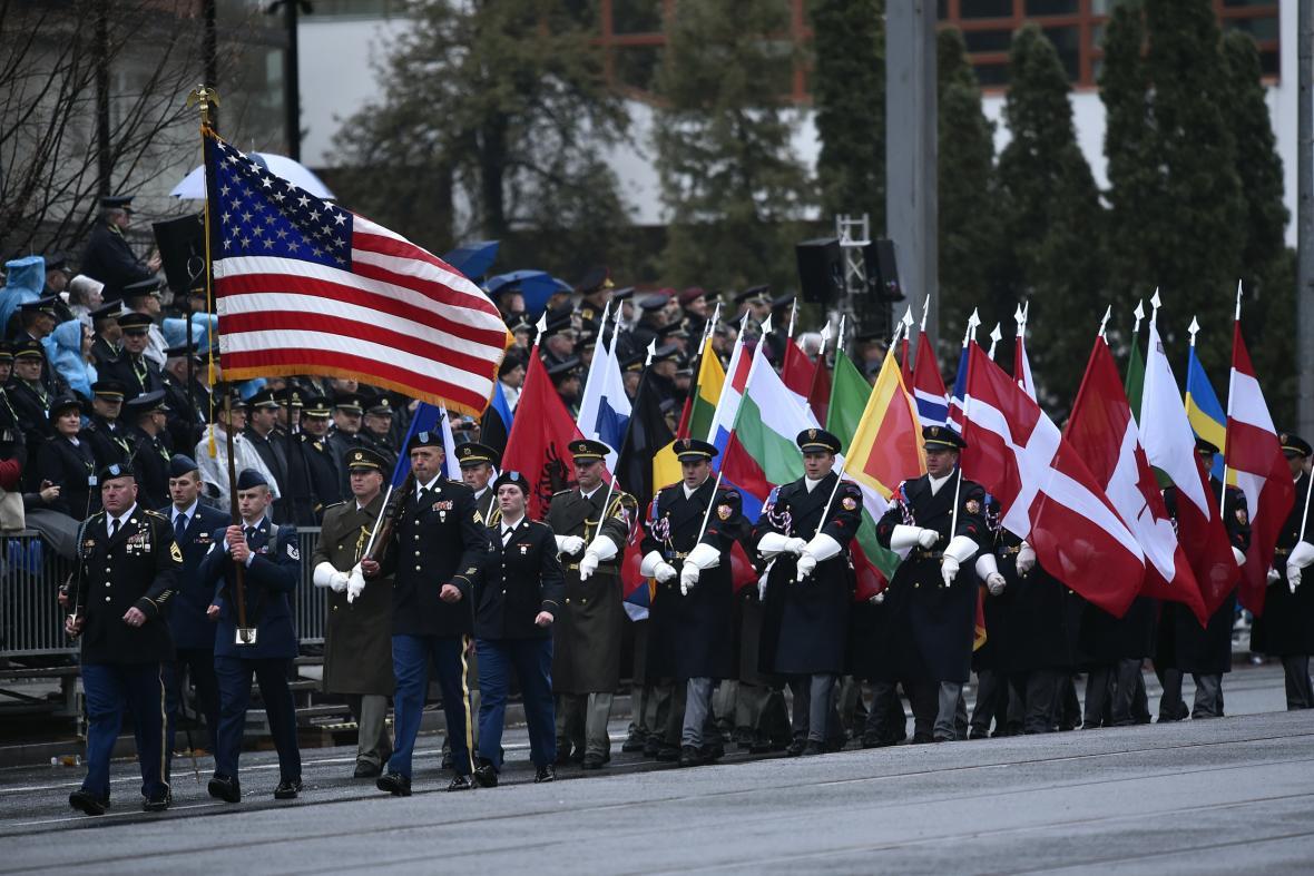 Zástupci armády USA (vlevo) a vojáci s vlajkami států NATO na vojenské přehlídce v Praze na Evropské třídě