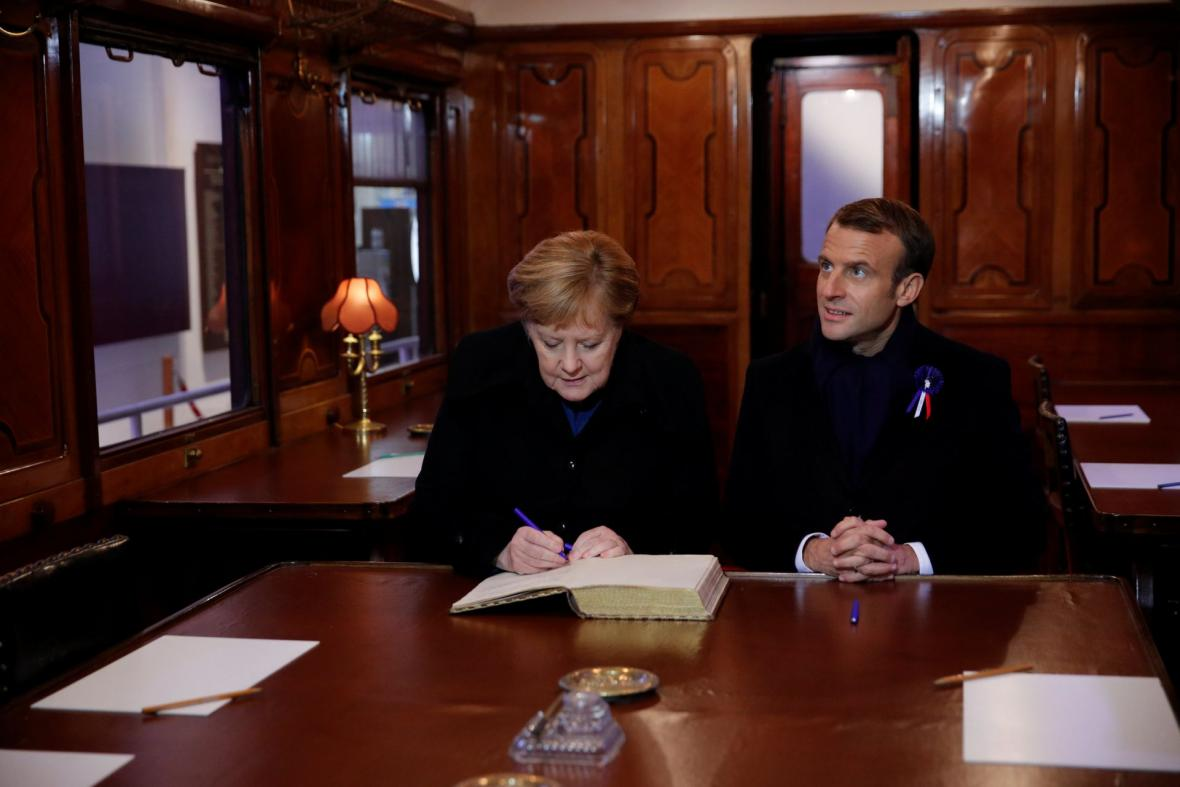Emmanuel Macron a Angela Merkelová se zapsali do návštěvní knihy v replice vagonu, kde bylo podepsáno příměří v roce 1918