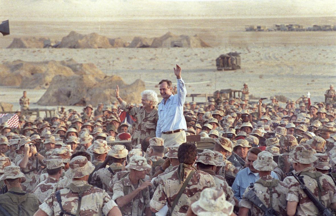 George Bush starší a jeho žena Barbara zdraví americké vojáky při Dnu díkuvzdání v Saúdské Arábii. Snímek je z roku 1990.