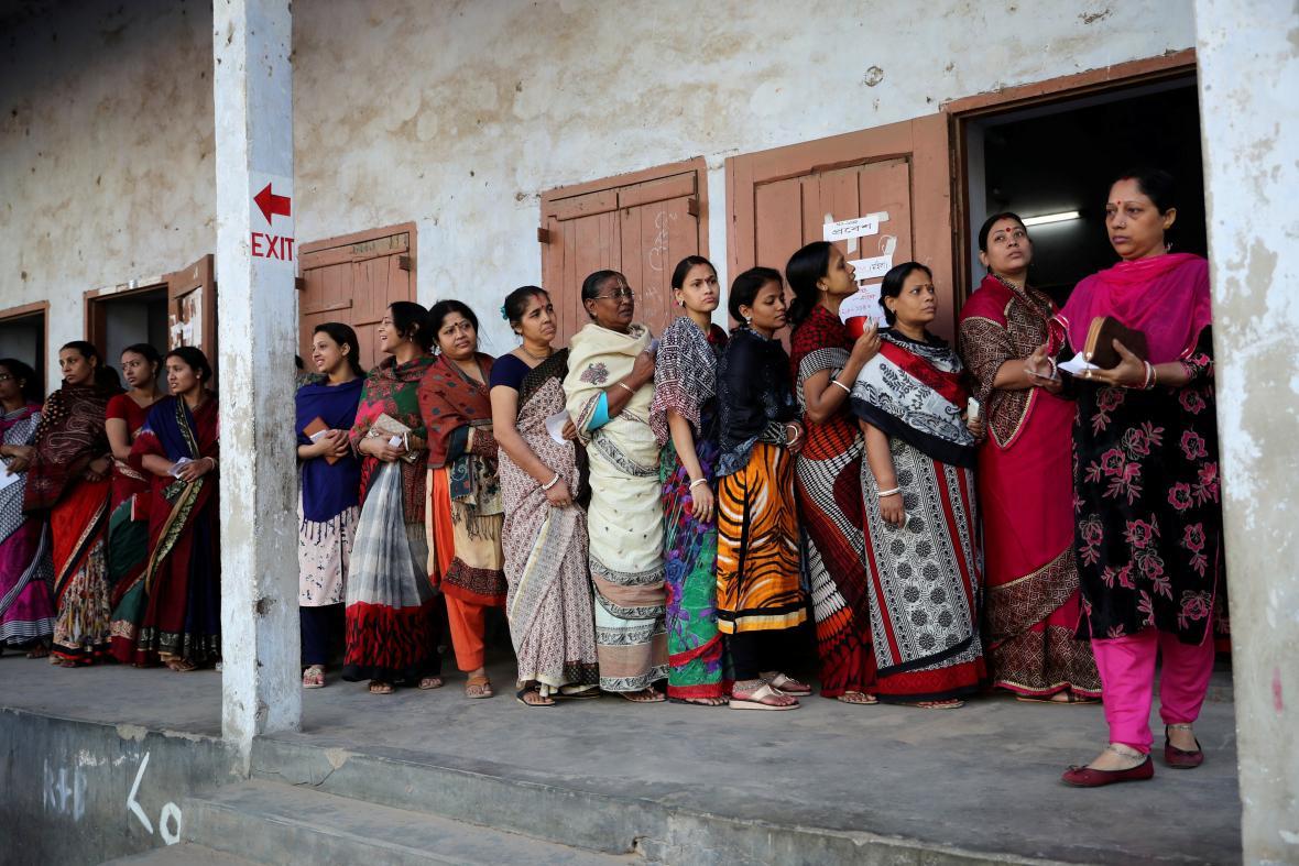 Lidé čekají ve frontě před jednou z volebních místností v Dháce