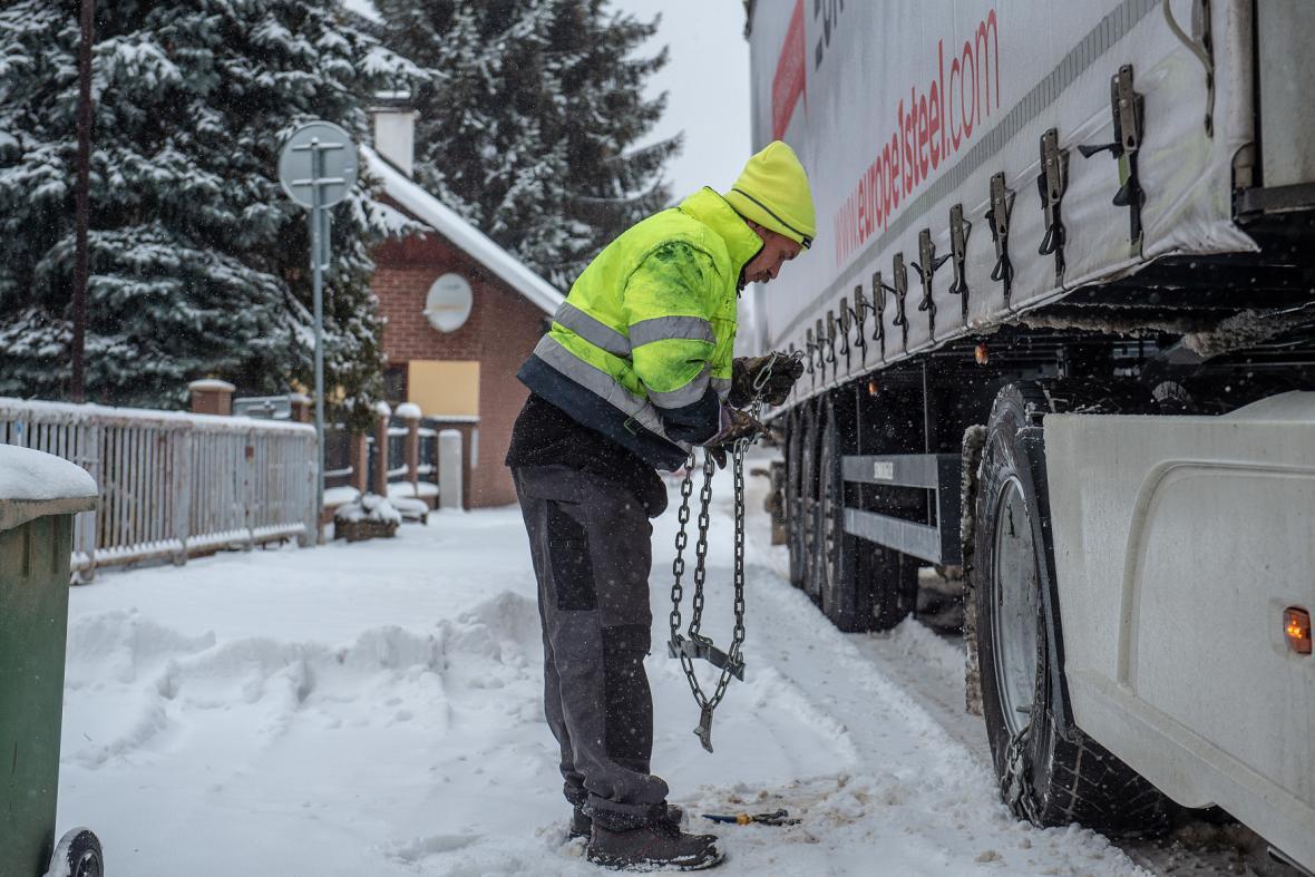 Řidič kamionu nasazuje sněhové řetězy