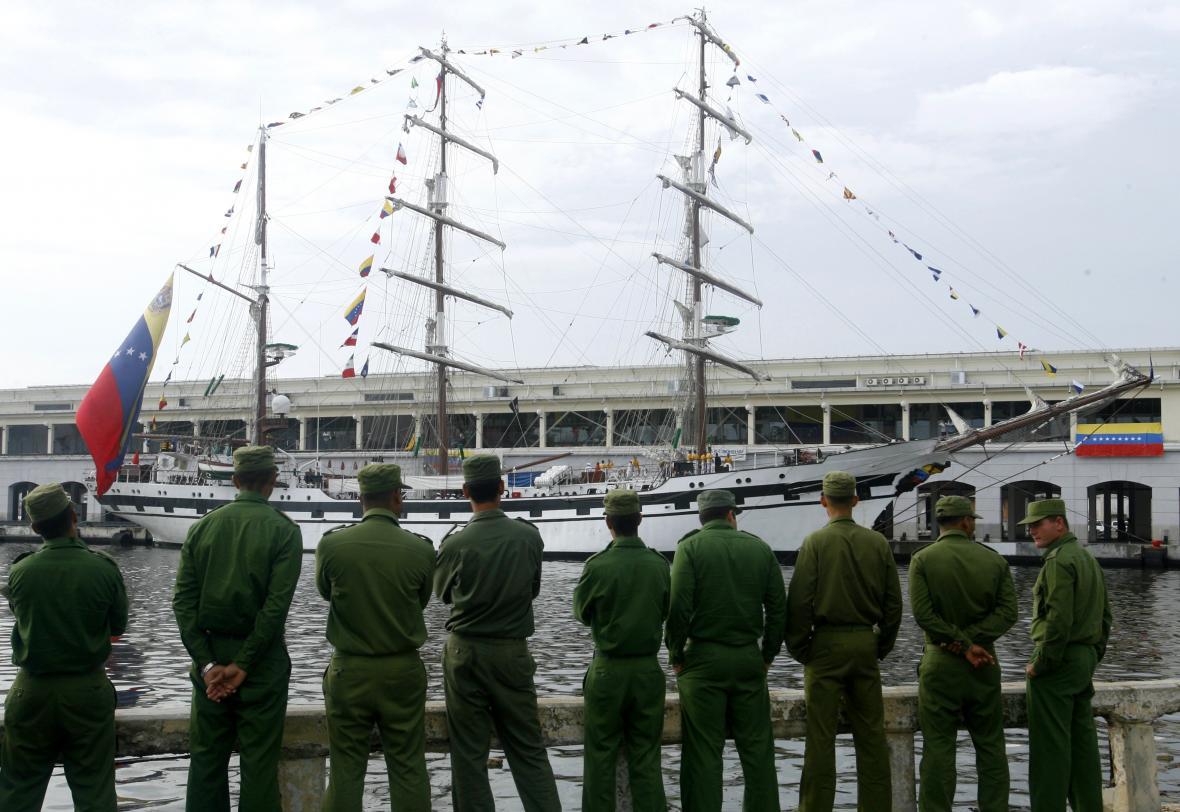 Kubánští vojáci sledují příjezd venezuelské lodi se studenty vojenské školy v roce 2010