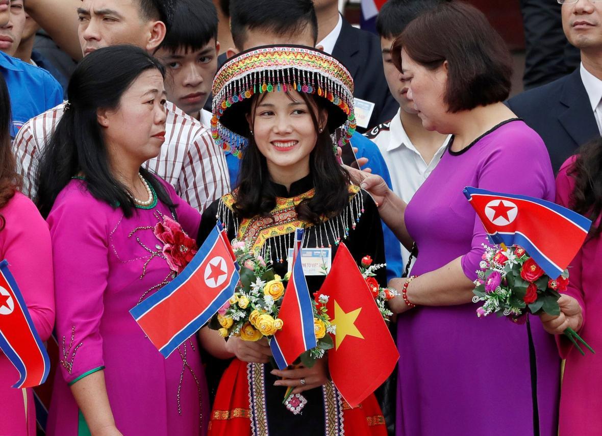 Žena s vlaječkami KLDR a Vietnamu čeká na severokorejského vůdce Kim Čong-una na nádraží ve vietnamském Dong Dangu