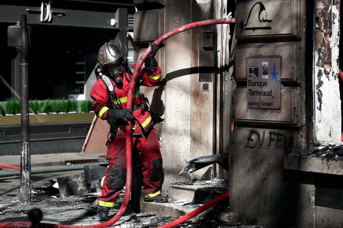 Hasič u banky Banque Tarneaud, kterou demonstranti předtím zapálili