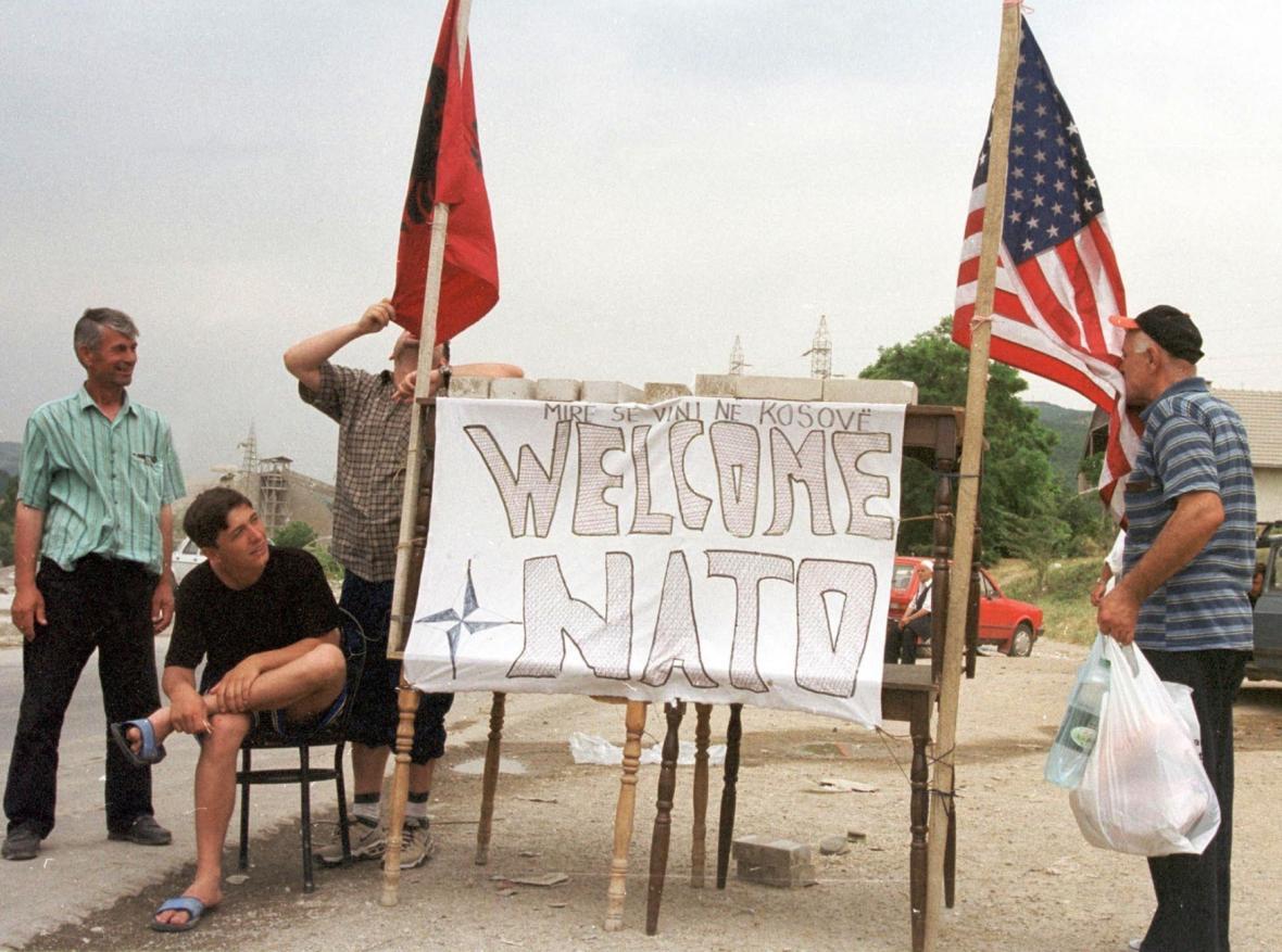 Kosovští Albánci líbají vlajky USA a Kosovské osvobozenecké armády při návratu do vlasti přes makedonsko-kosovskou hranici (15. 6. 1999)