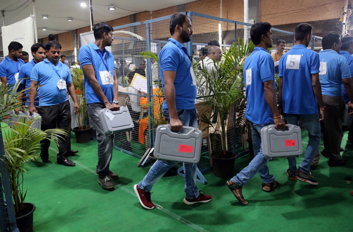 Členové volební komise v Bombaji nesou stroje na sčítání hlasů