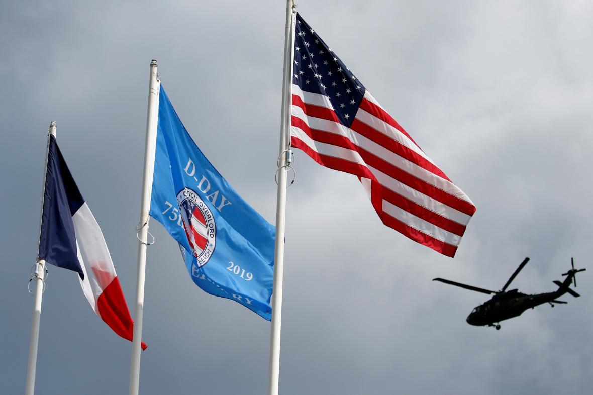 Americká vojenská helikoptéra nad vlajkami Francie a USA