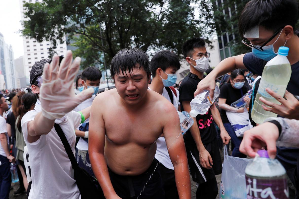 Demonstranti se omývají po použití slzného plynu