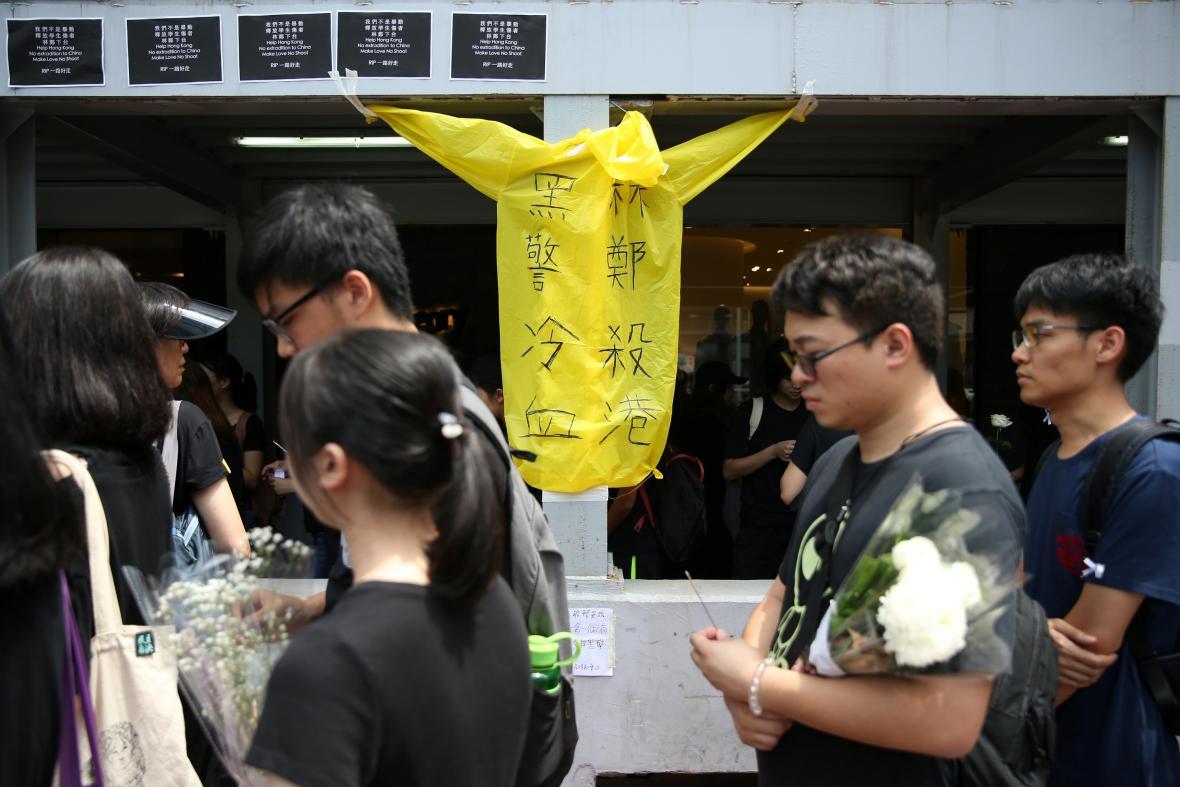 Lidé u památníku muže, který se zabil v sobotu, když se snažil pověsit transparent