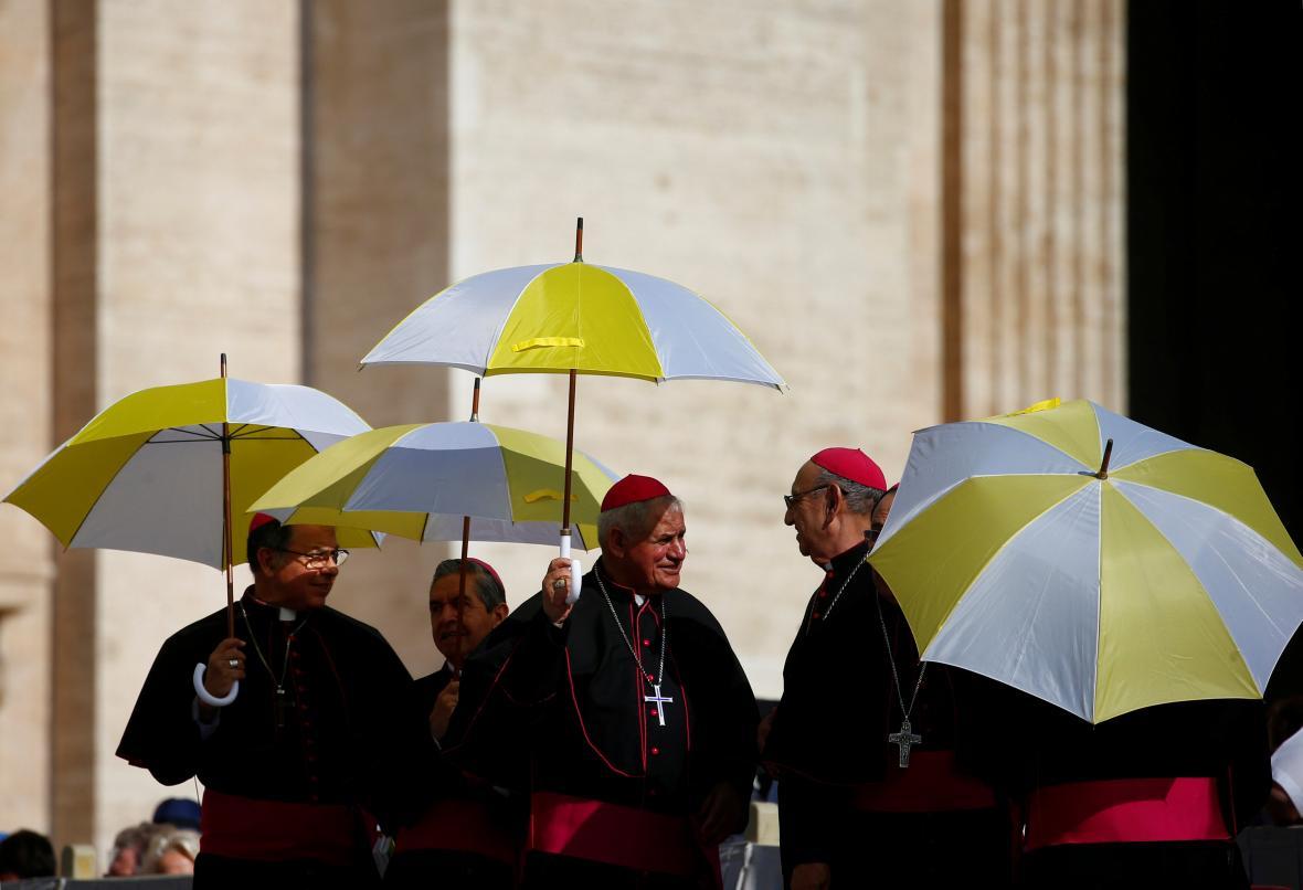 Duchovní ve Vatikánu se slunečníky