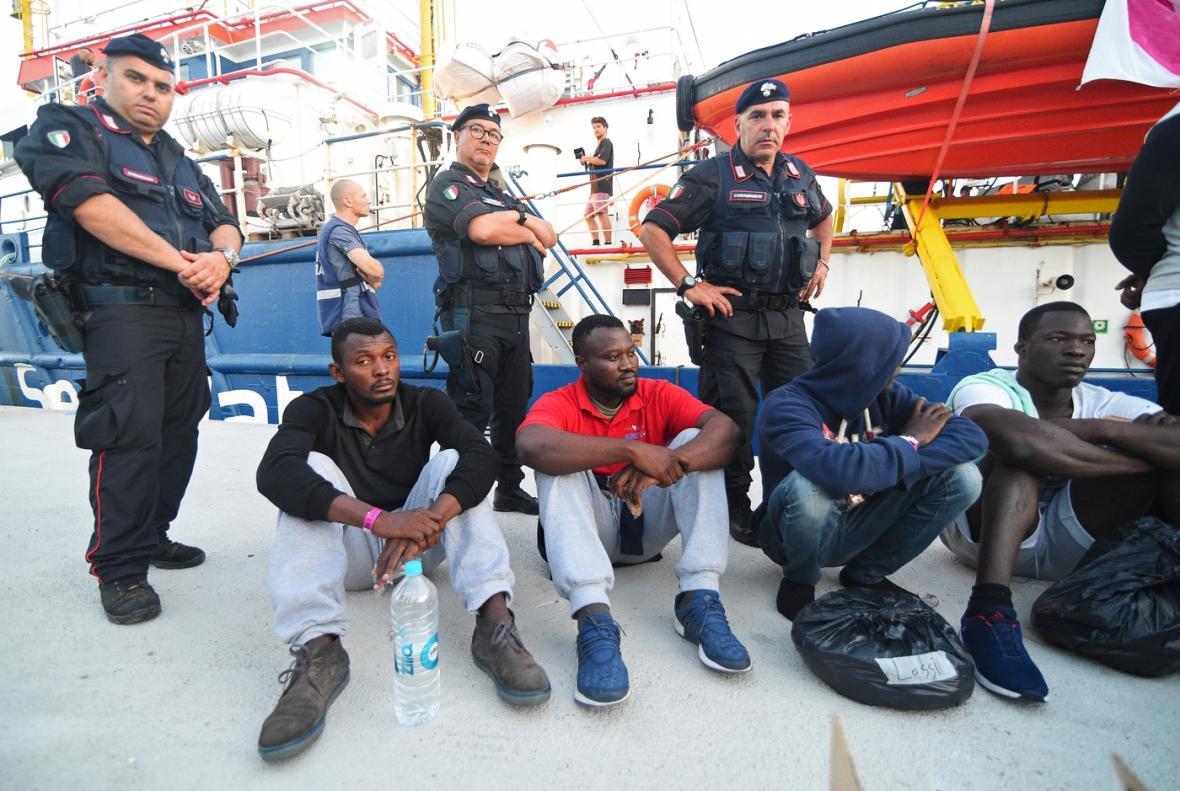 Italští policisté kolem migrantů, kteří vystoupili z lodě.