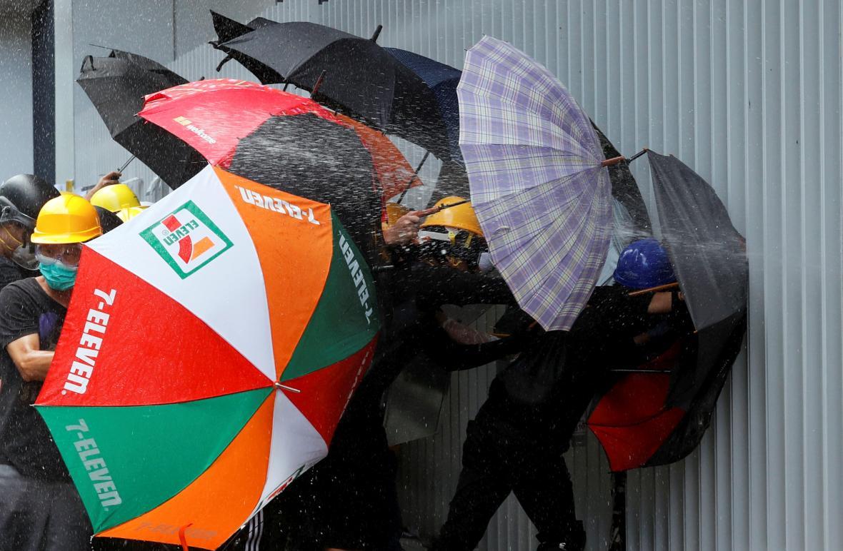 Demonstranti se chrání deštníky před pepřovým sprejem
