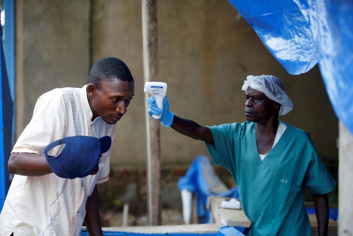 Zdravotník kontroluje teplotu jednomu z pacientů v konžském zdravotnickém centru