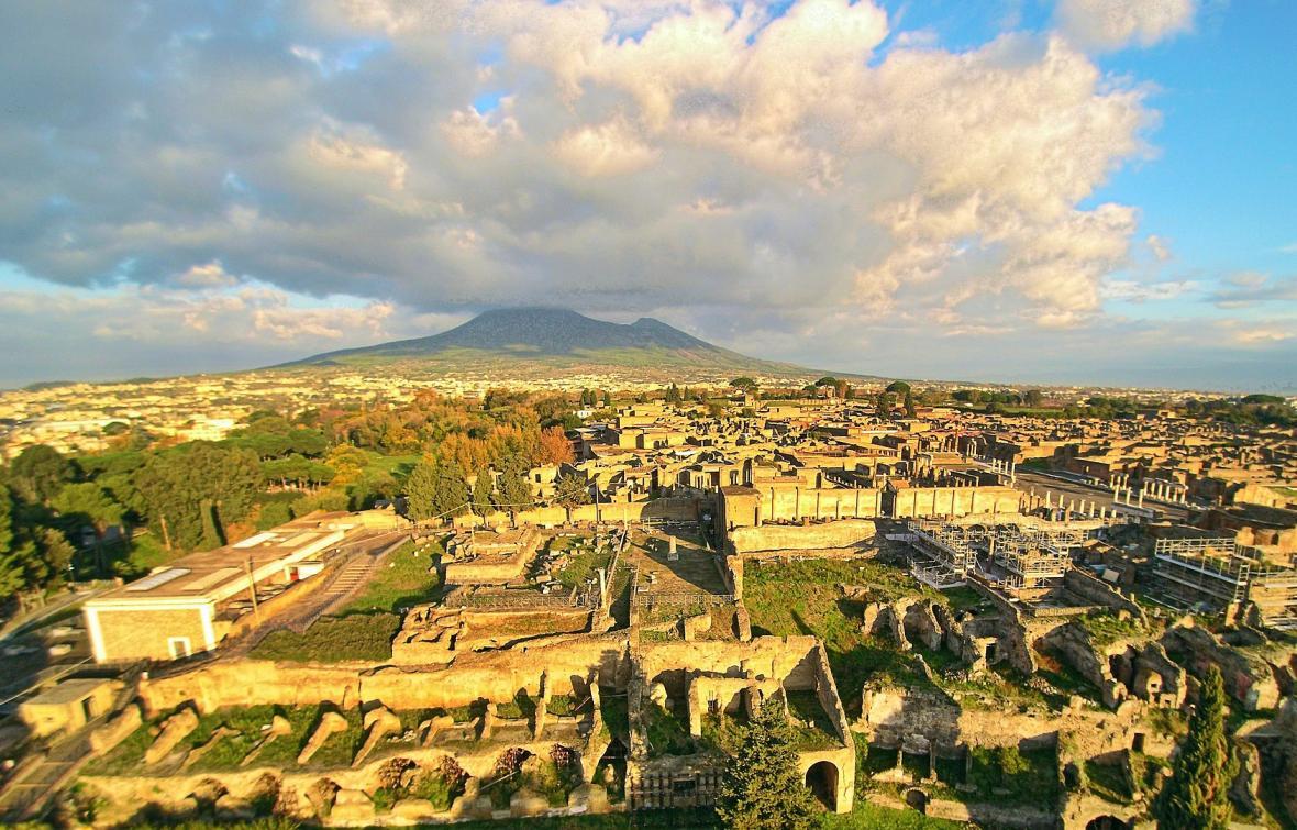 Ruiny Pompejí. V pozadí se tyčí po výbuchu zborcený kužel Vesuvu
