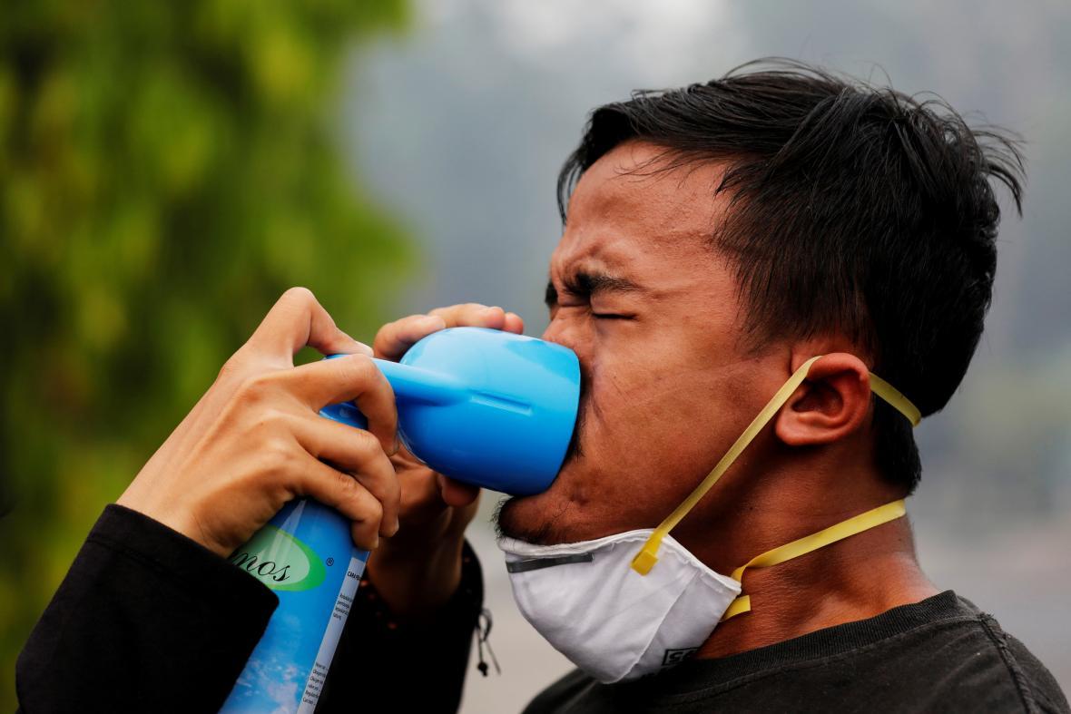 Jeden z demonstrujících v Indonésii dostává dýchnout kyslíku, protože oblast je stále zahalená dýmem z vypalovaných lesů