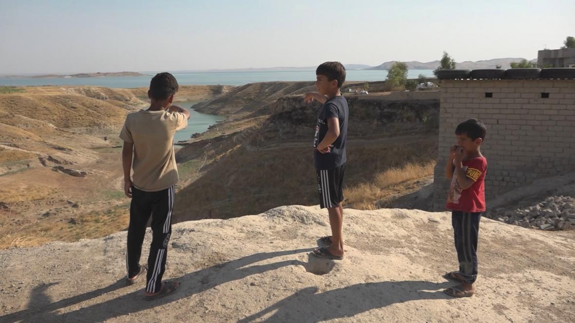 Irácké děti ukazují na přehradu u Mosulu
