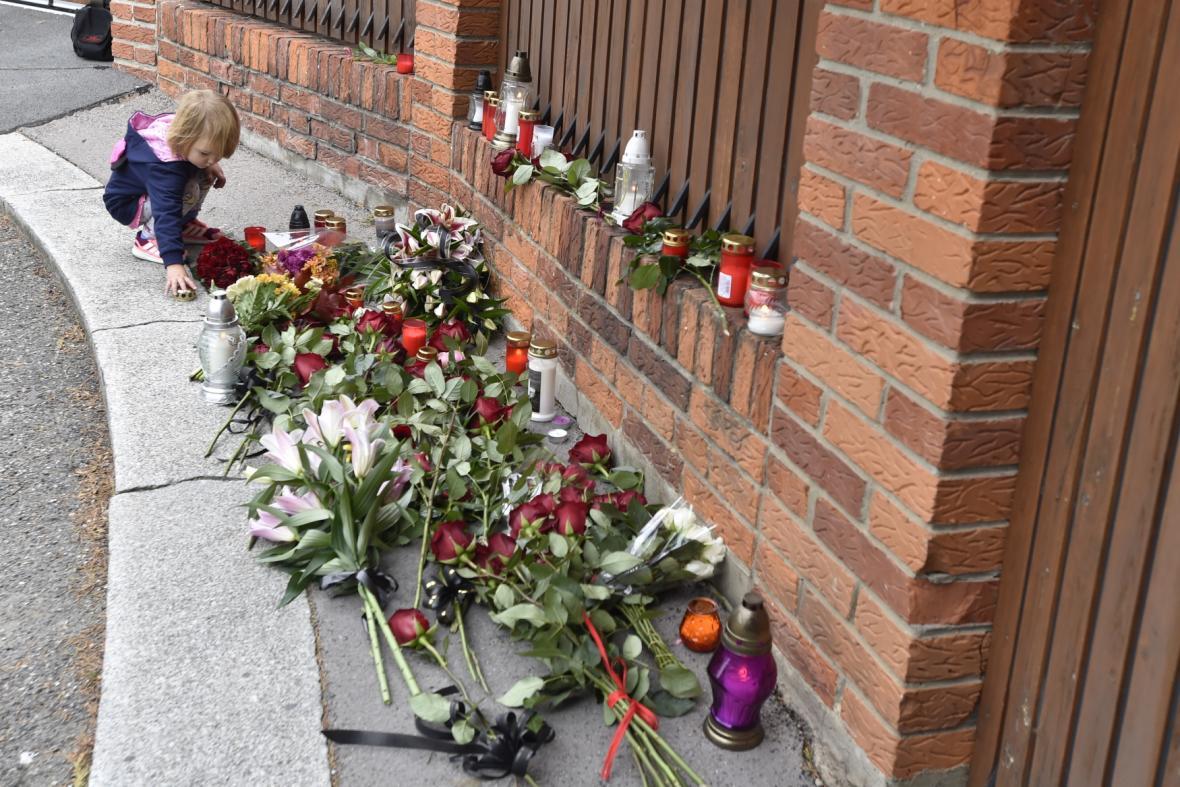 Dívka pokládá svíčku 2. října 2019 před vilou Karla Gotta na pražské Bertramce