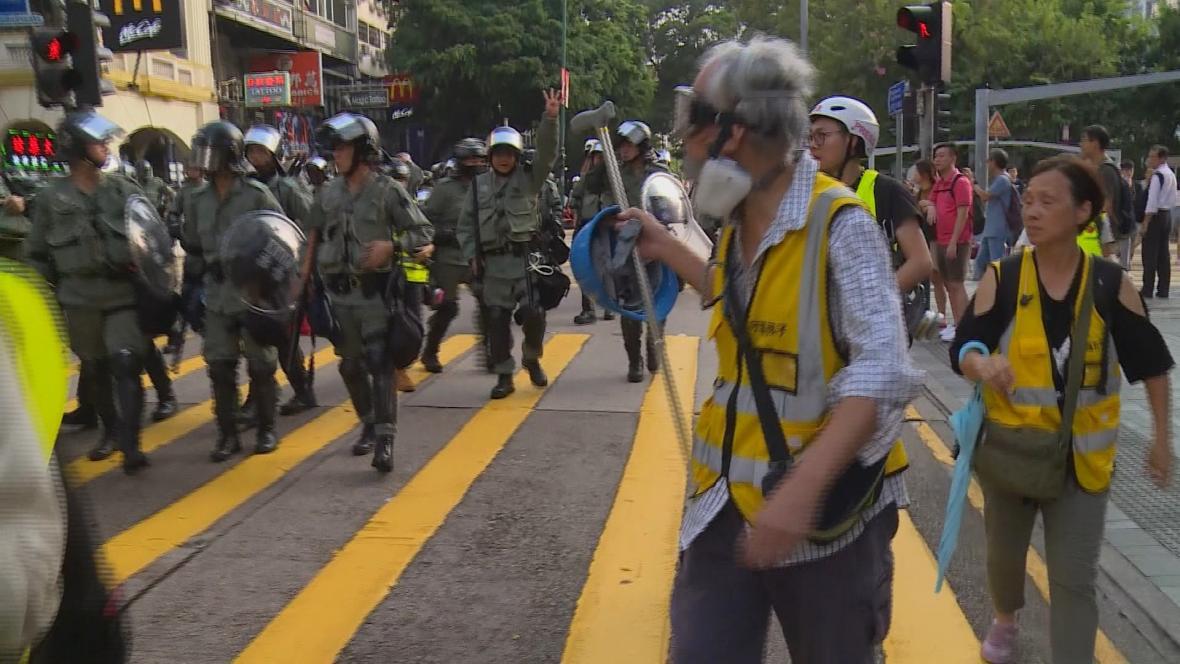 Wong s dalšími dobrovolníky se snaží udržet bezpečnostní složky a protestující od sebe