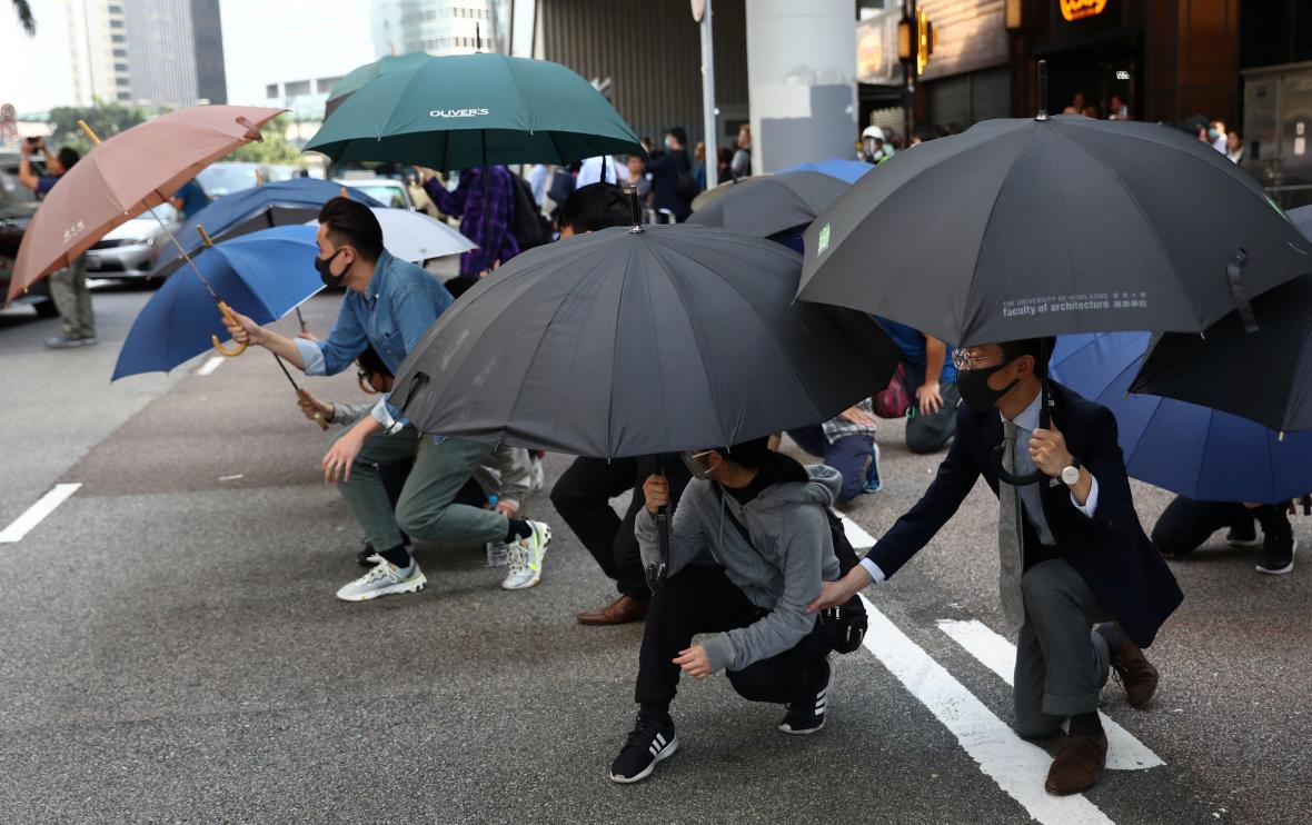 Lidé se kryjí deštníky