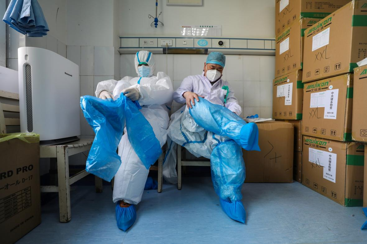 Zdravotníci v nemocnici v čínském Wu-chanu si oblékají ochranné obleky
