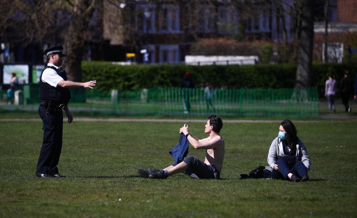 Policista hovoří s lidmi v londýnském Greenwich Parku