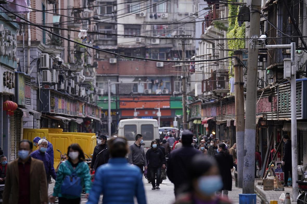 Do ulic Wu-chanu se lidé dál vydávají s rouškami