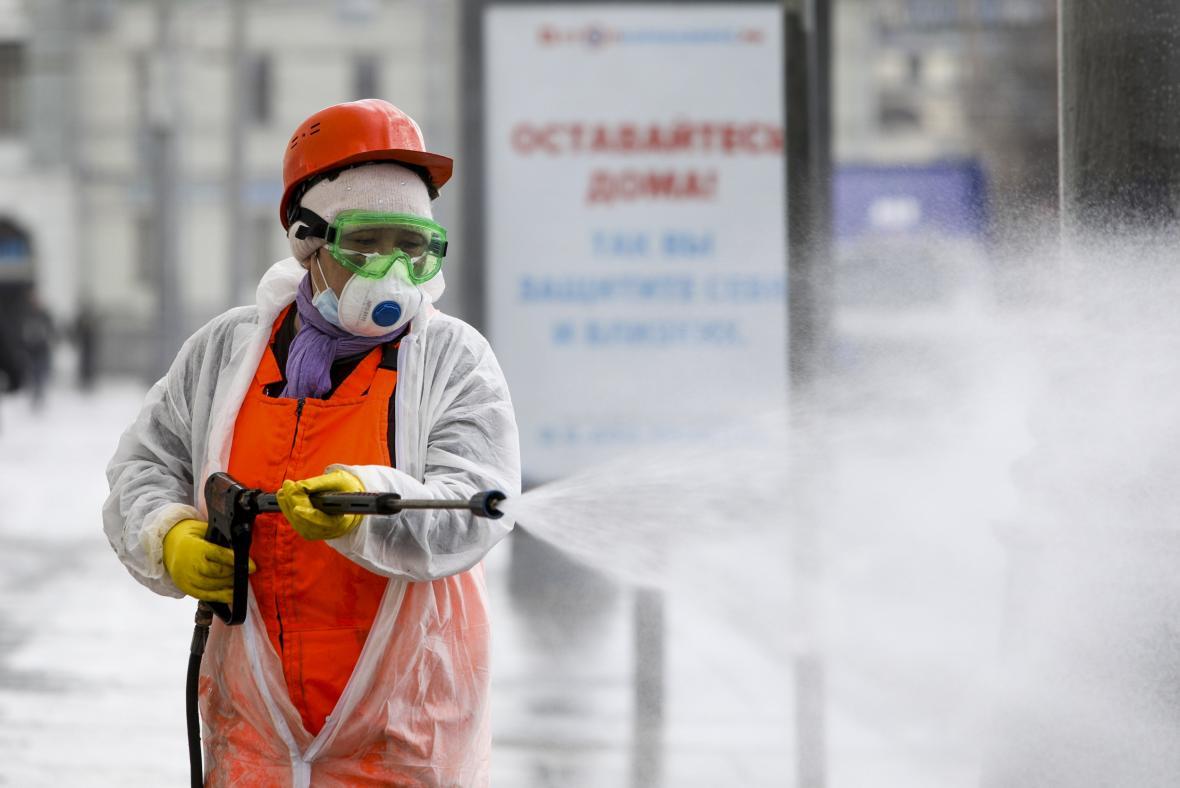 Dezinfekce ulice v Moskvě. V pozadí cedule s nápisem