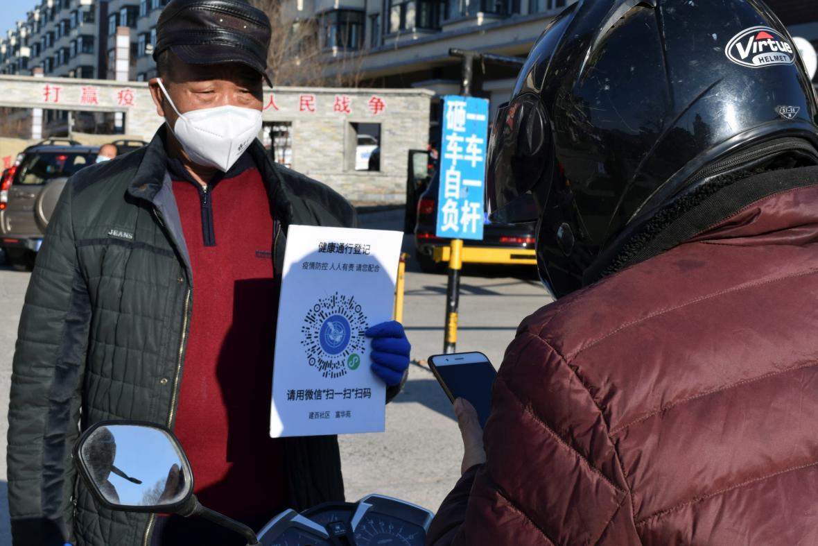 Muž ve městě Suej-fen-che ukazuje QR kód, který potvrzuje jeho zdravotní stav