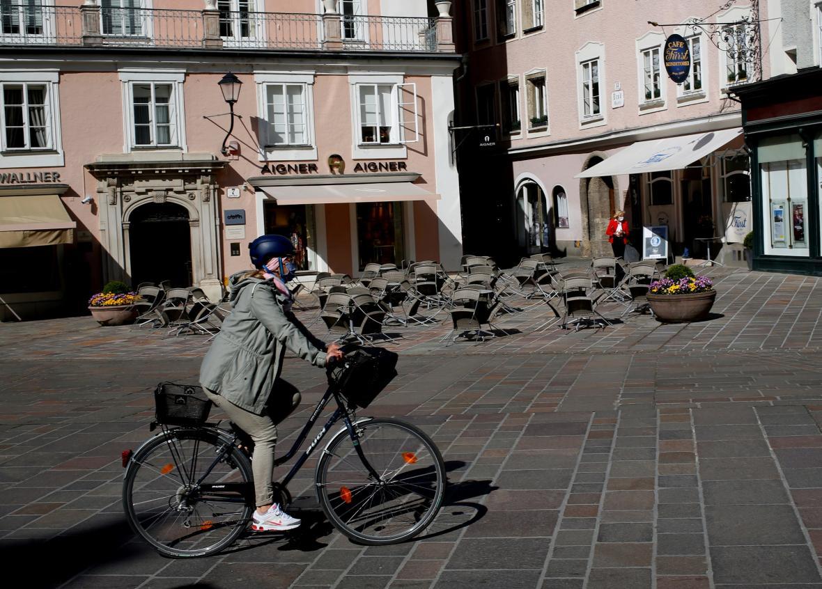 Žena na kole před uzavřenou kavárnou v rakouském Salzburgu