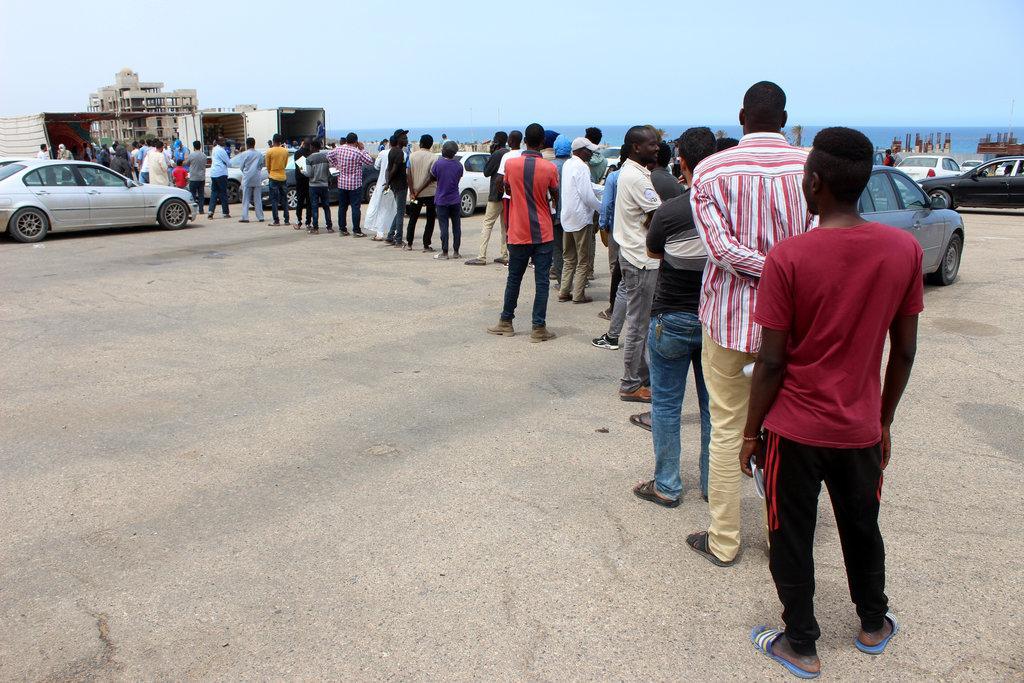 Migranti čekající na potravinové balíčky od UNHCR