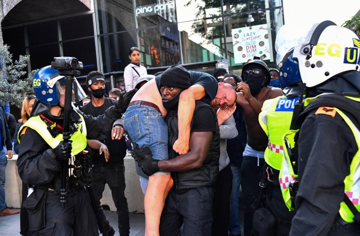 Fotka protestujícího, nesoucího zraněného bělocha, se dostala na titulní strany britských novin
