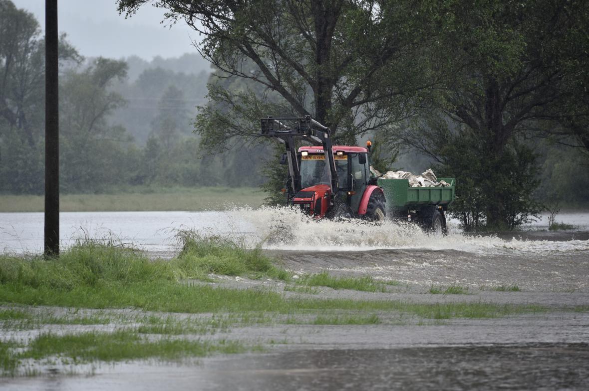Traktor s vlekem projíždí po zaplavené cestě kvůli rozlité Smědé ve vesnici Předlánce, místní části obce Višňová.