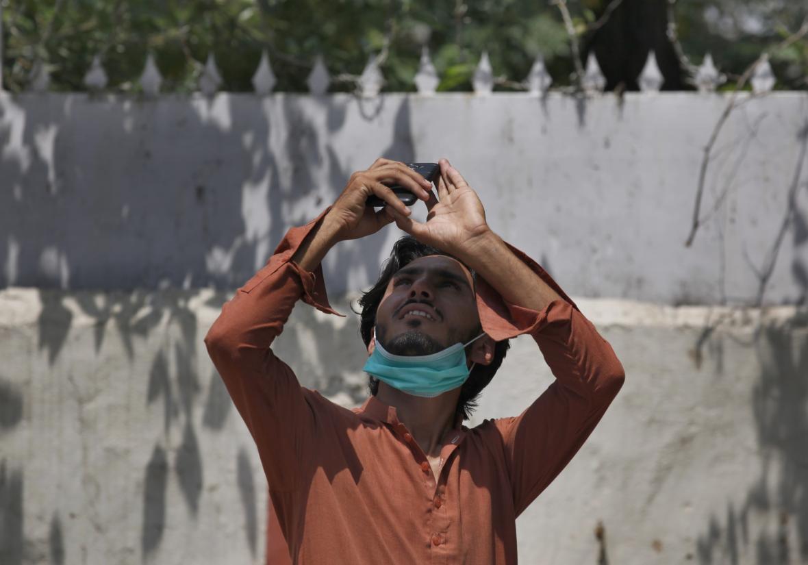 Muž se snaží vyfotografovat částečné zatmění slunce v Pákistánu
