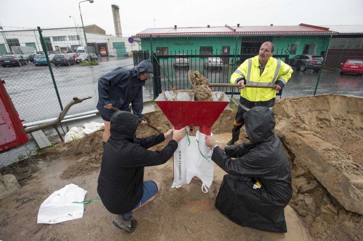 Dobrovolníci plní pytle pískem na ochranu před záplavami 29. června 2020 v Dolních Ředicích na Pardubicku, kde se kvůli silným dešťům vylil z břehů Ředický potok.