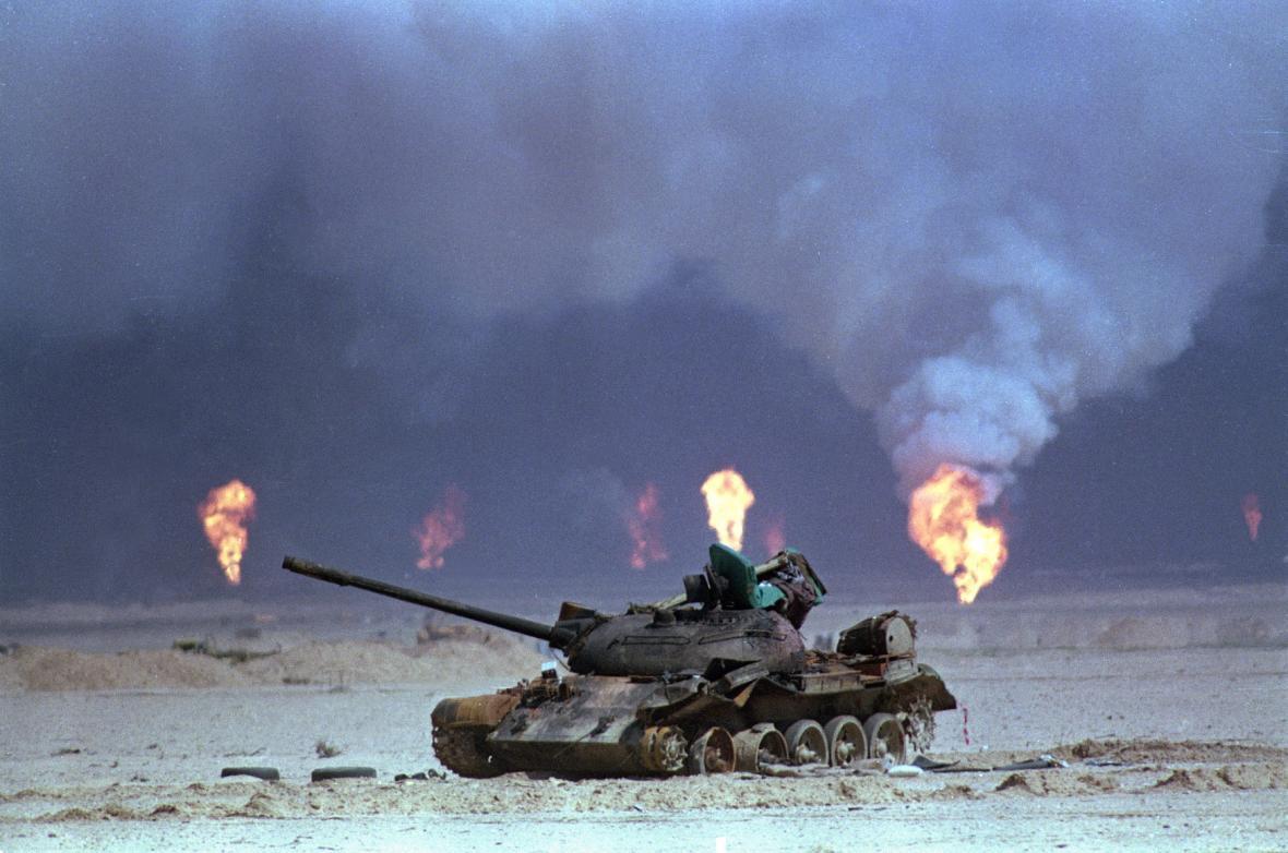 Zničený irácký tank během války v Perském zálivu, v pozadí hoří ropná pole