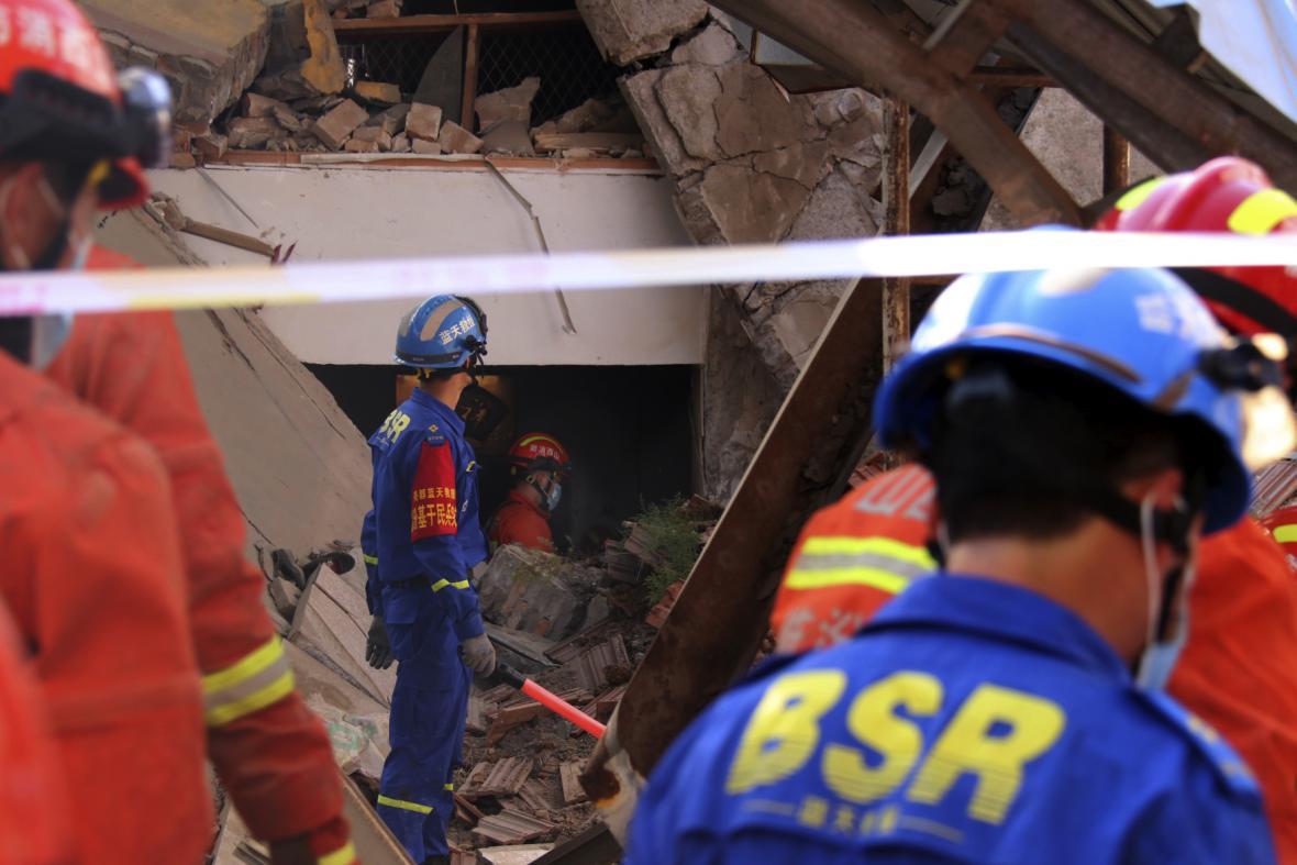 Záchranáři prohledávají trosky zřícené budovy s restaurací