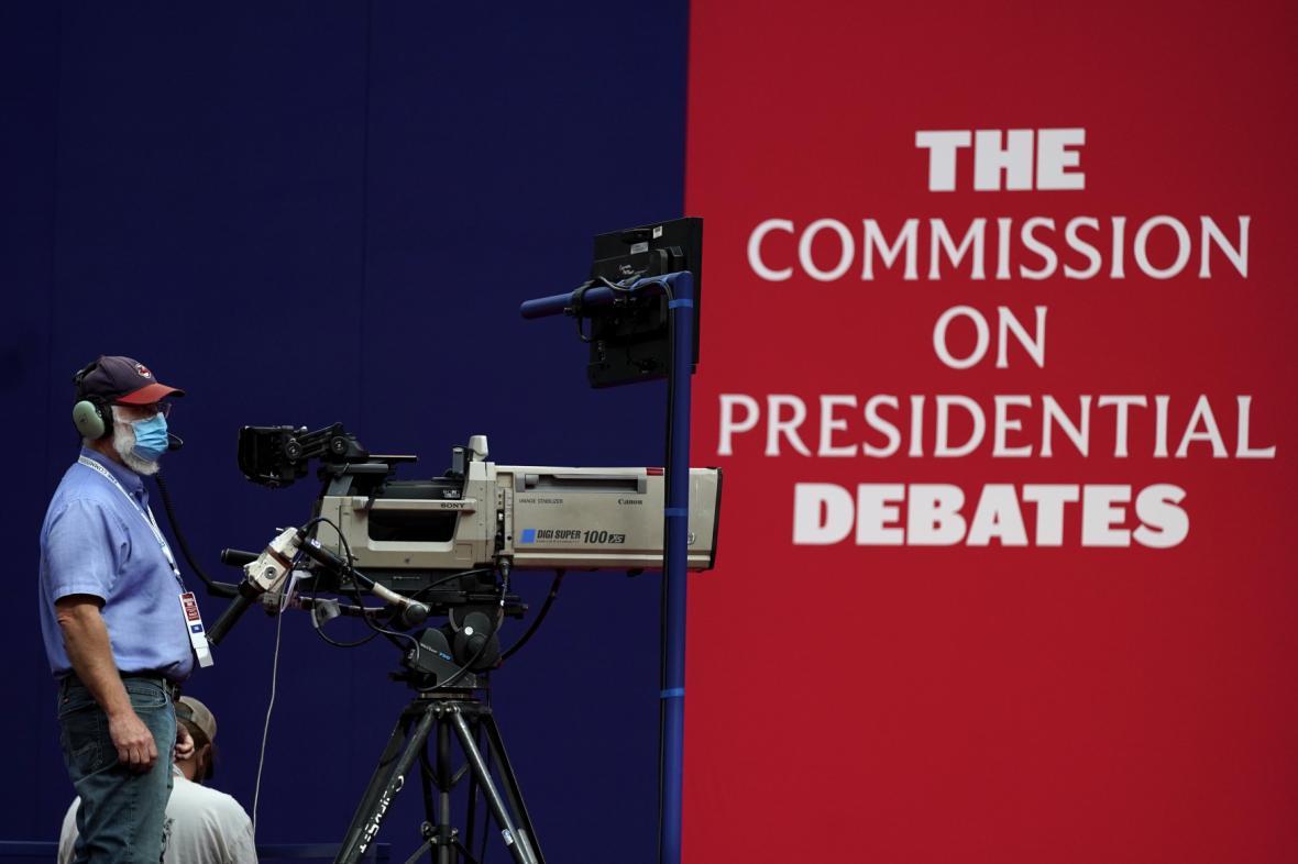 Kameraman stojí u svého vybavení při přípravě na natáčení debaty
