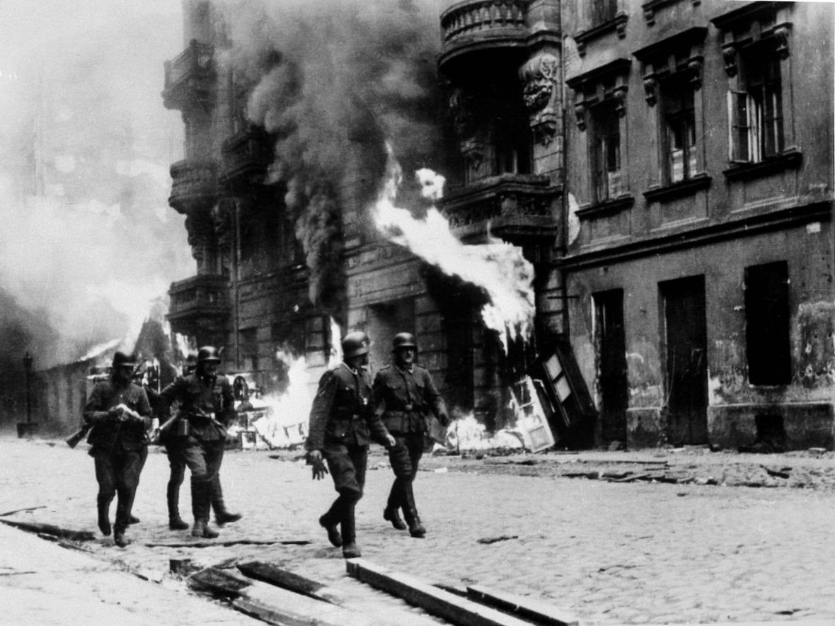 Němečtí vojáci procházejí hořícím varšavským ghettem
