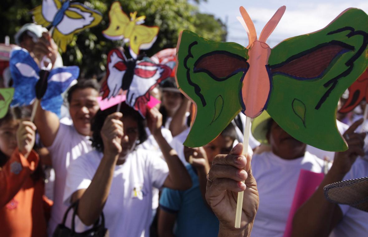 Lidé držící symbol sester Mirabaových - papírového motýla při pochodu proti násilí na ženách