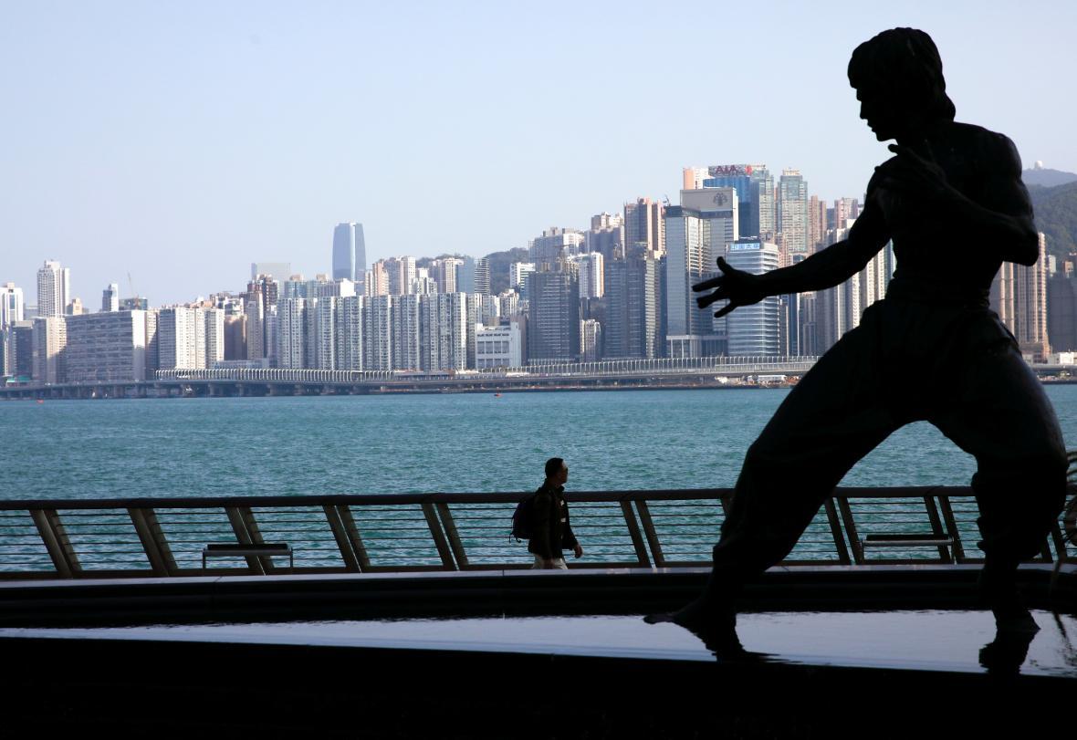 Panorama Hongkongu v kontrastu sochy Bruce Lee. Hollywoodský herec a populizátor bojového umění tady zemřel