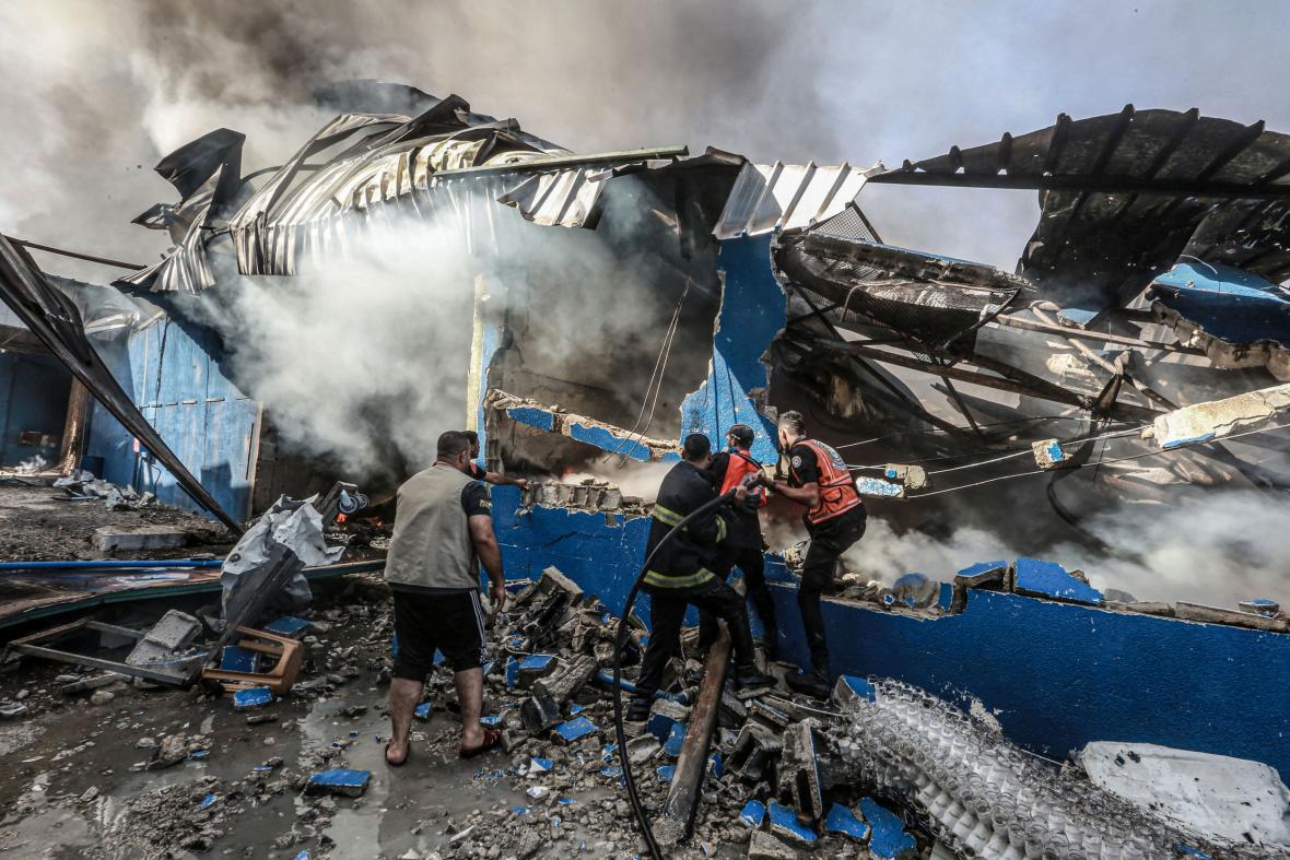 Členové palestinské civilní obrany se pokoušejí uhasit oheň v továrně po zásahu izraelskými dělostřeleckými granáty