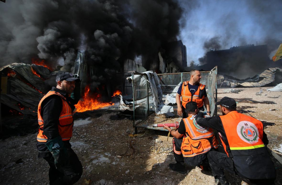Hašení požáru v továrně v Gaze po zásahu granáty